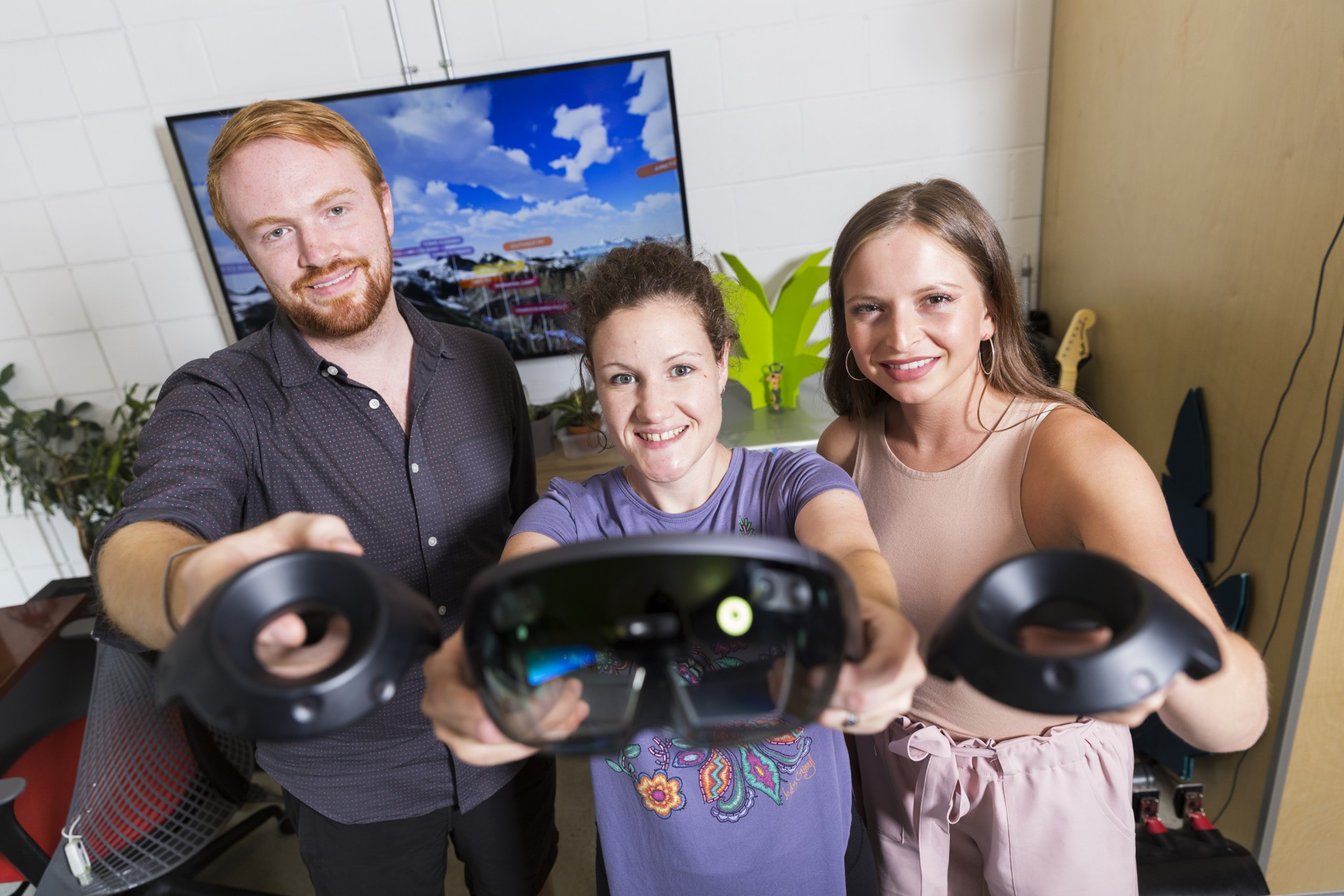 three people holding up VR equipment