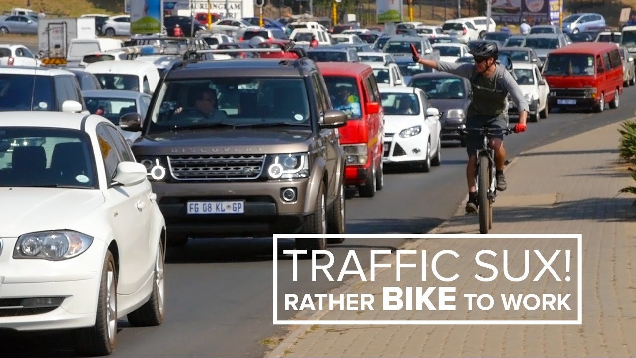 person biking beside huge amount of commuter traffic